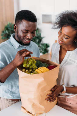 Young couple taking out grapes from paper bag with fruits