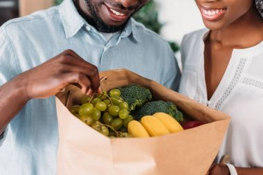 Cropped view of young couple holding paper bag with grapes, bananas and broccoli