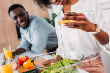 Cropped view of african american woman adding oil in salad while smiling boyfriend standing beside