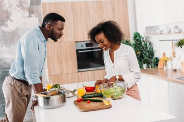 Smiling couple standing at table with vegetables, salad and pasta in saucepan