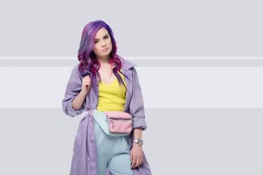 beautiful young woman in purple trench coat with waist pack on creative background
