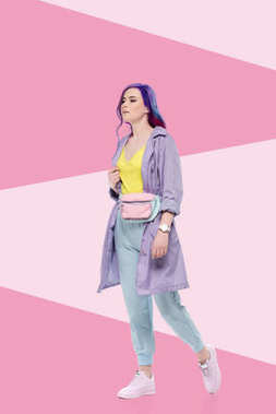 stylish young woman in purple trench coat with waist pack on creative background