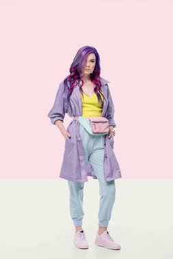 attractive young woman in purple trench coat with waist pack on creative background
