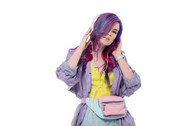 fashionable young woman with colorful hair in purple trench coat listening music with headphones isolated on white