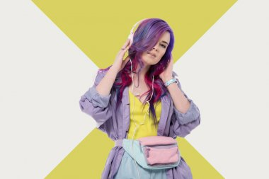 fashionable young woman with colorful hair in purple trench coat listening music with headphones