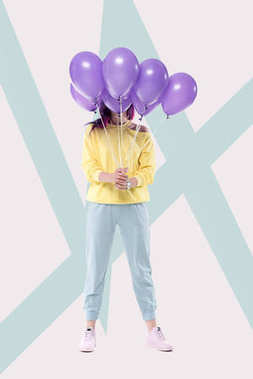 woman holding bunch of helium balloons on creative background