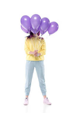stylish young woman covering face with bunch of helium balloons isolated on white