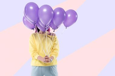 woman covering face with bunch of helium balloons on creative background