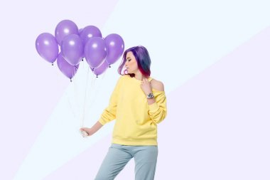 attractive young woman holding bunch of helium balloons on creative background