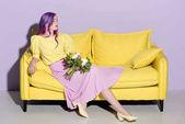 Fotografie schöne junge Frau, die auf gelbe Couch mit Blumenstrauß