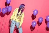 schöne junge Frau in transparentem Regenmantel mit Luftballons auf Rot