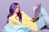 Fotografie vážné mladá žena s barevnými vlasy čtení knihy v posteli