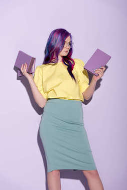 attractive young woman with colorful hair holding books on pink
