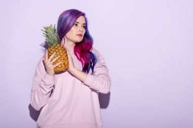 beautiful young woman with colorful hair and pink sweatshirt holding pineapple