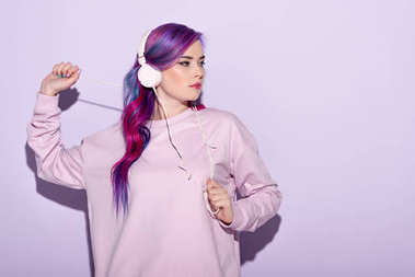 dancing young woman in pink clothes listening music with headphones