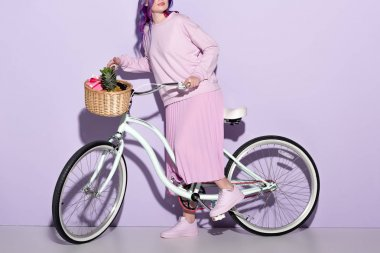 Cropped shot of young woman in pink clothing on bicycle with pineapple and bananas in basket stock vector