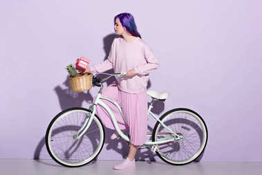 beautiful young woman in pink clothing on bicycle with pineapple and gift box in basket