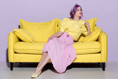thoughtful young woman sitting on yellow couch