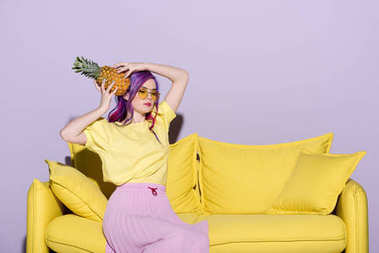 beautiful young woman sitting on yellow couch and holding pineapple near head