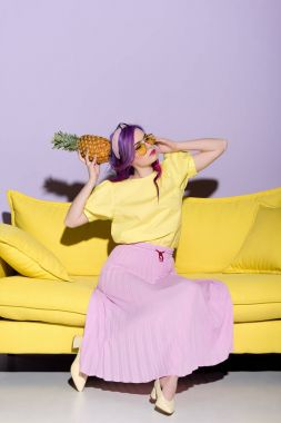 beautiful young woman on yellow couch holding pineapple near head