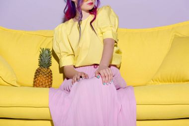 cropped shot of young woman sitting on yellow couch with pineapple