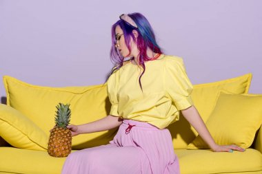 beautiful young woman sitting on yellow couch with pineapple