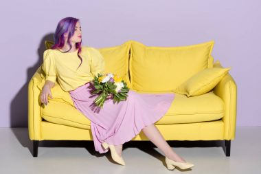 beautiful young woman sitting on yellow couch with floral bouquet