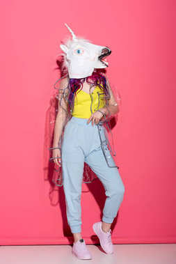 stylish woman in fashionable transparent raincoat and unicorn mask on red