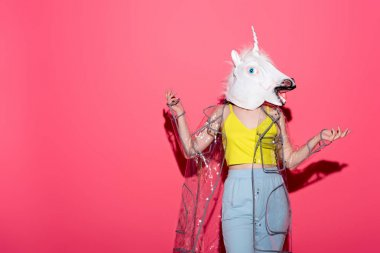 funny woman in fashionable transparent raincoat and unicorn mask on red