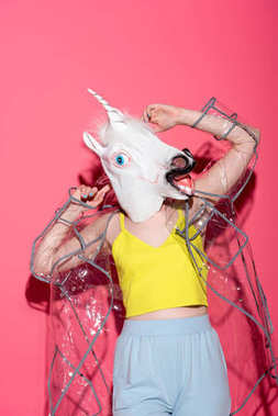 ridiculous woman in fashionable transparent raincoat and unicorn mask on red