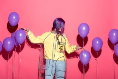 stylish young woman in transparent raincoat with balloons on red