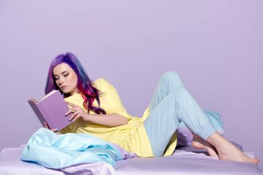 concentrated young woman with colorful hair reading book in bed