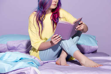 cropped shot of young woman with colorful hair reading book in bed