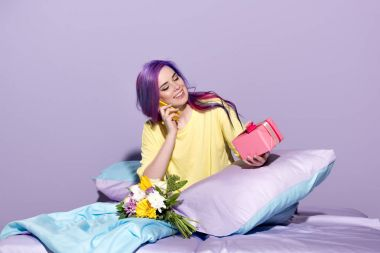 beautiful young woman with gift box and flowers sitting in bed and talking by phone