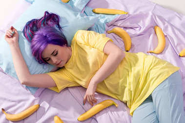 high angle view of young woman lying in bed with bananas