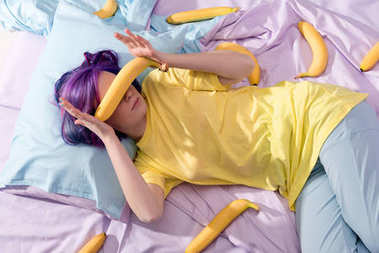 high angle view of young woman lying in bed with bananas and covering face