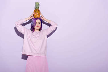 attractive young woman in pink sweatshirt holding pineapple on head