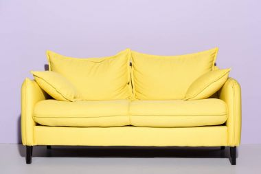 comfy yellow couch in front of pink wall