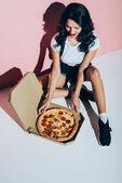 Fotografie pohled z vysokého úhlu stylová žena a dodání krabice s pizzou na podlaze na růžové pozadí