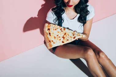 cropped shot of stylish woman with piece of pizza on pink backdrop