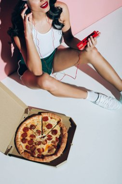 cropped shot of smiling woman with retro music player and delivery box with pizza on pink background
