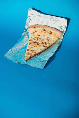 close up view of piece of italian pizza on foil on blue background