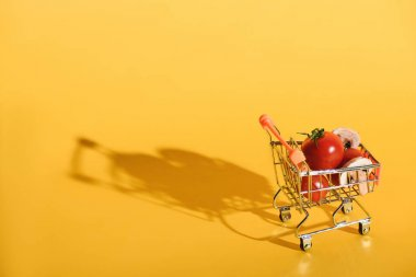 close up view of little shopping cart with fresh ingredients for pizza on orange backdrop