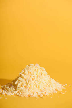 close up view of grated cheese on orange background