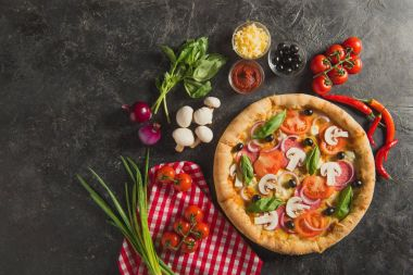 flat lay with italian pizza and fresh ingredients on dark surface