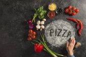 vista parziale della mano femminile, ingredienti freschi e lettering pizza fatta di farina sulla superficie scura