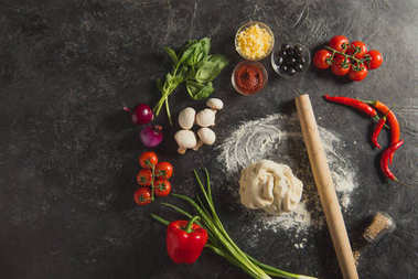 flat lay with rolling pin, raw dough and fresh ingredients for pizza on dark surface