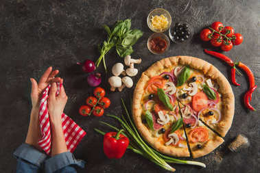 cropped shot of female hands and cooked italian pizza with fresh ingredients on dark tabletop