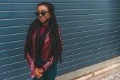 krásná usměvavá mladá africká americká žena v módní kabát a brýle pózuje venku