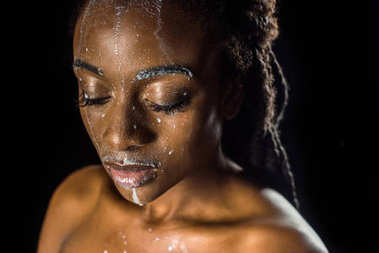 beautiful sensual young african american woman with spilled milk on face isolated on black